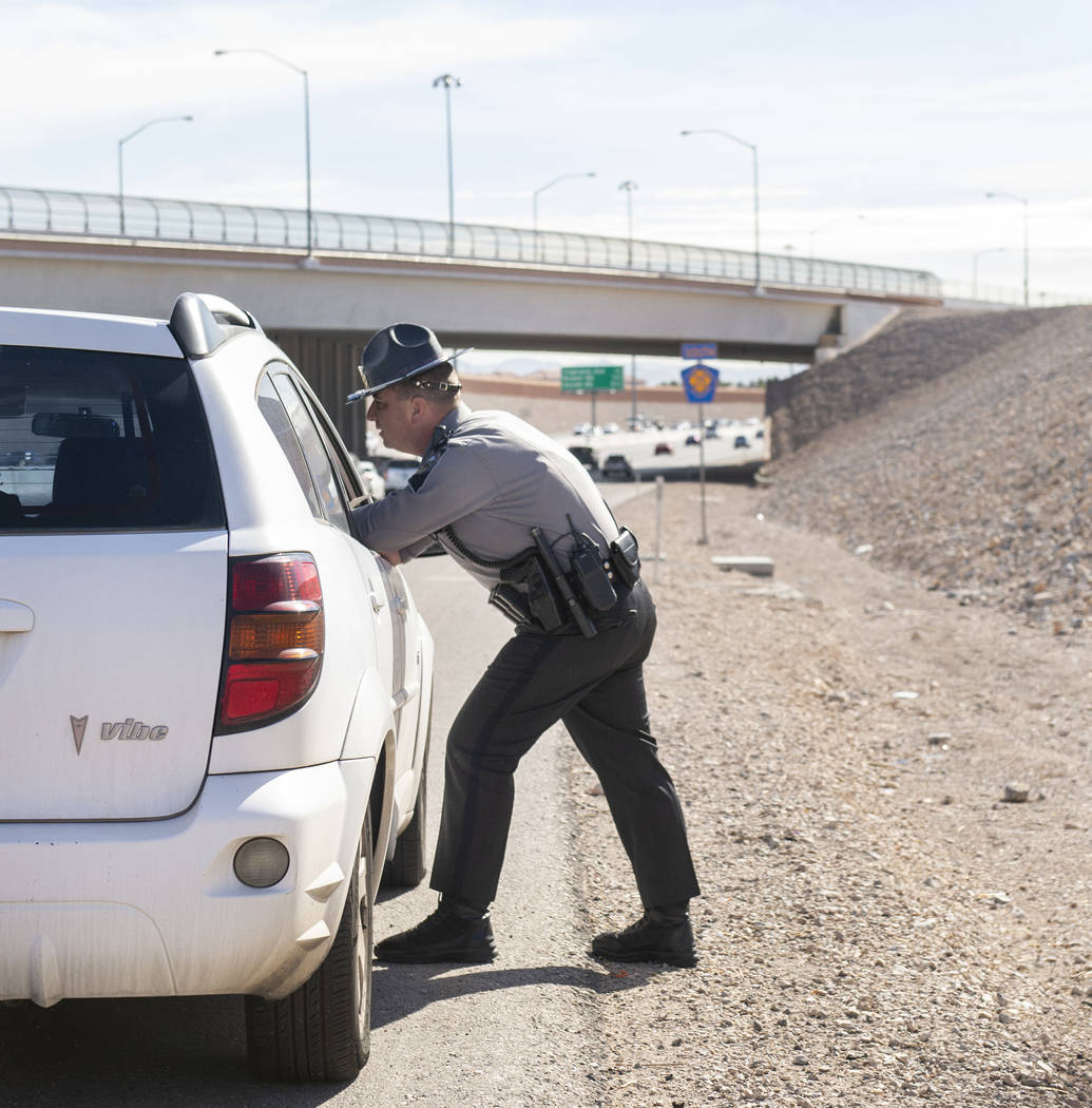 Nevada Highway Patrol public information and education officer Jason Buratczuk speaks with a driver after pulling her over for speeding on the 215 Beltway in Las Vegas on Tuesday, Nov. 20, 2018. C ...