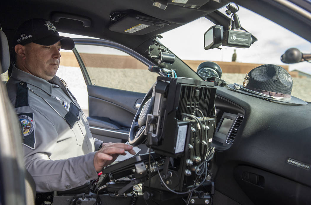 Nevada Highway Patrol public information and education officer Jason Buratczuk files information into a computer after pulling over a driver for speeding on the 215 Beltway in Las Vegas on Tuesday ...