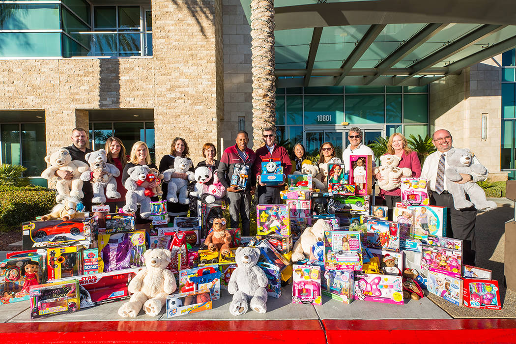 Clark County Commissioner Lawrence Weekly, center, gathers with employees of The Howard Hughes Corp. last year to collect donated toys. The annual drive is organized by Weekly for children who are ...