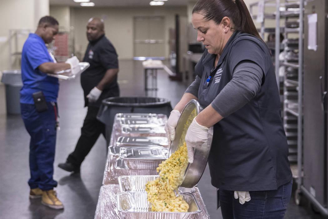 Hot food rescue food handler Lisa Garcia, right, prepares tilapia to be transferred to Three Square on Tuesday, November 13, 2018, at Aria, in Las Vegas. Benjamin Hager Las Vegas Review-Journal