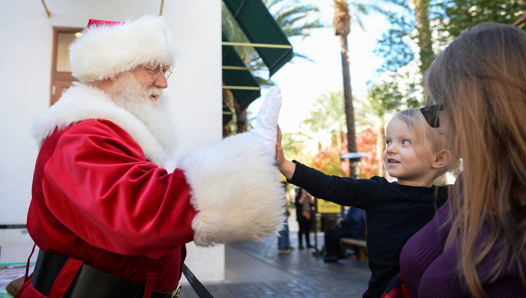 Santa Claus high-fives Henderson resident Emilia Brodie, 2, along with mother Monica Brodie at the District at Green Valley Ranch in Henderson, Saturday, Nov. 24, 2018. Caroline Brehman/Las Vegas ...
