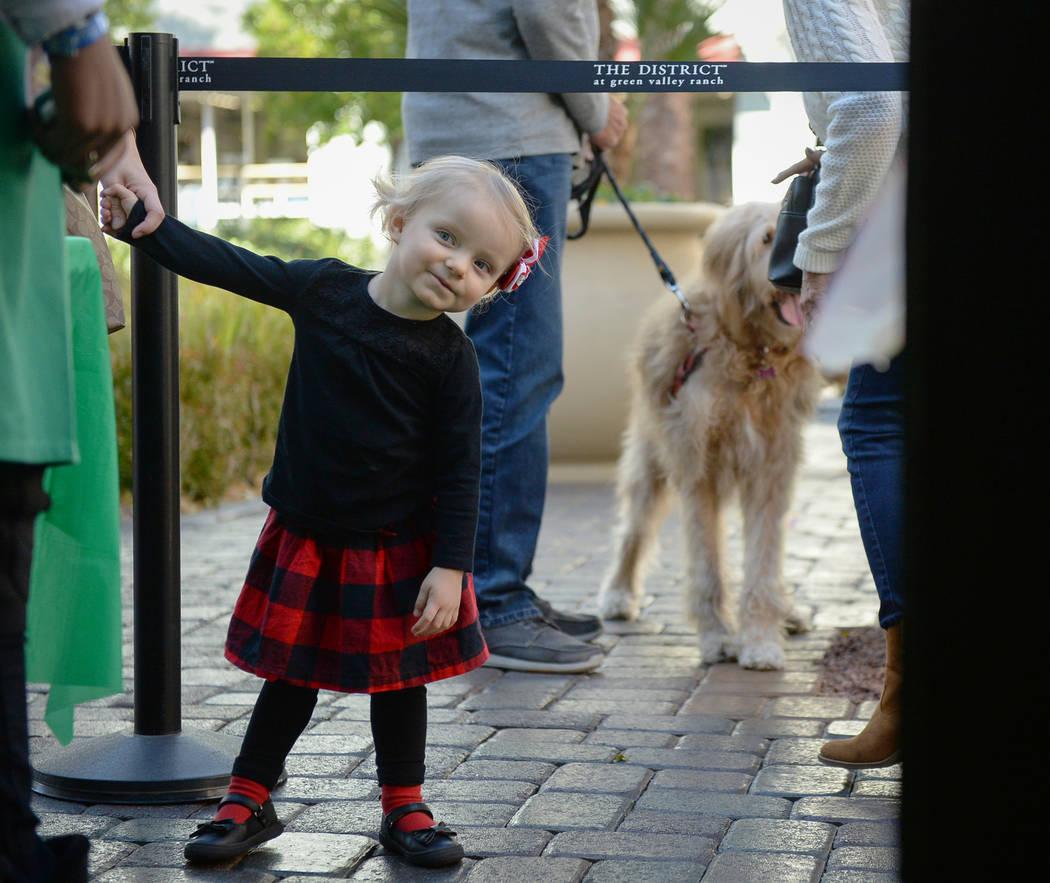 Emilia Brodie, 2, peers around the corner to get a peek at Santa Claus at the District at Green Valley Ranch in Henderson, Saturday, Nov. 24, 2018. Caroline Brehman/Las Vegas Review-Journal