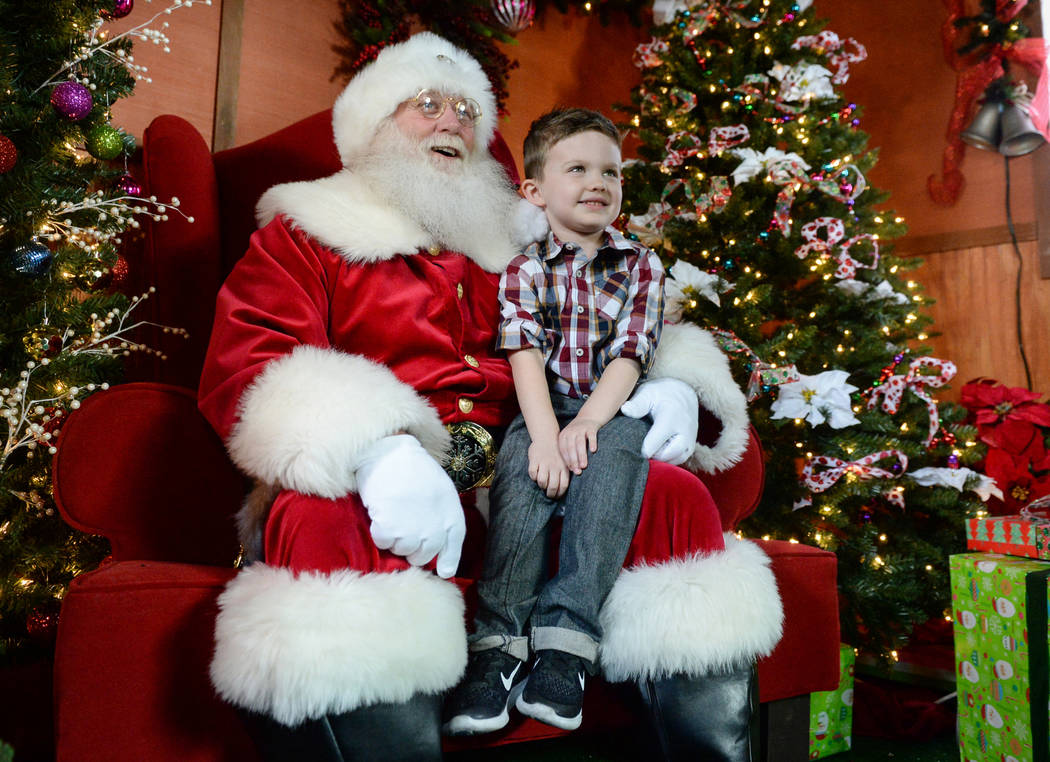 Maverick Willis, 5, from Henderson, sits on Santa Claus's lap, as they take a photograph together at the District at Green Valley Ranch in Henderson, Saturday, Nov. 24, 2018. Caroline Brehman/Las ...