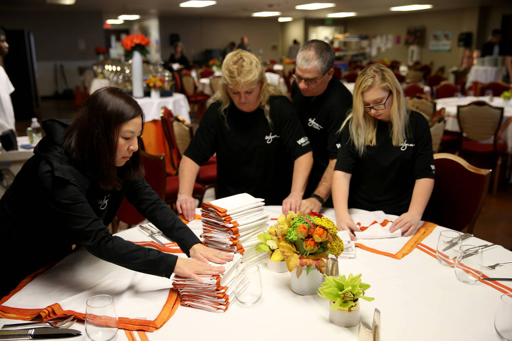 Wynn Las Vegas employees Ida Shek, left, and Candy Johnson, and Johnson's husband Gary and daughter Amanda, 14, prepare for Thanksgiving dinner catered by casino at the Shade Tree shelter for home ...