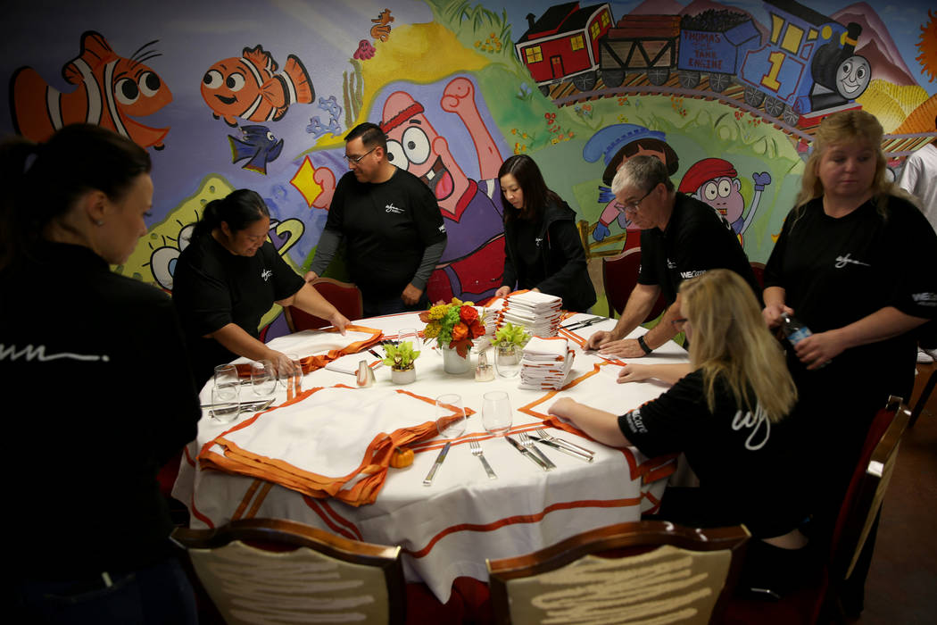 Wynn Las Vegas employees and family members, from left, Leslie Keating, Gerilyn Rocha, Steve Rocha, Ida Shek, Gary Johnson, Amanda Johnson, 14, and Candy Johnson prepare for Thanksgiving dinner ca ...