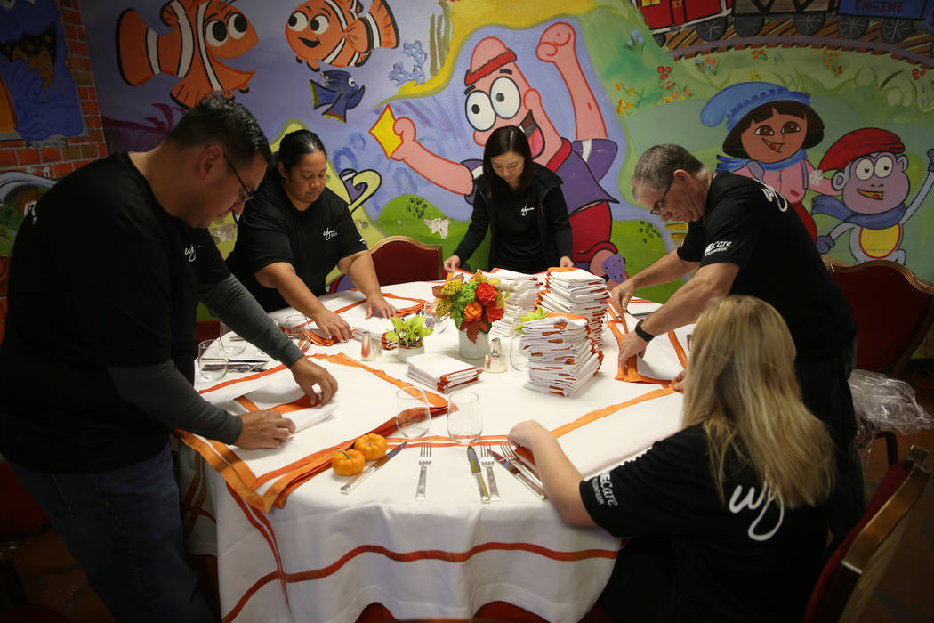 Wynn Las Vegas employees and family members, from left, Steve Rocha, Gerilyn Rocha, Ida Shek, Gary Johnson and Amanda Johnson, 14, prepare for Thanksgiving dinner catered by casino at the Shade Tr ...