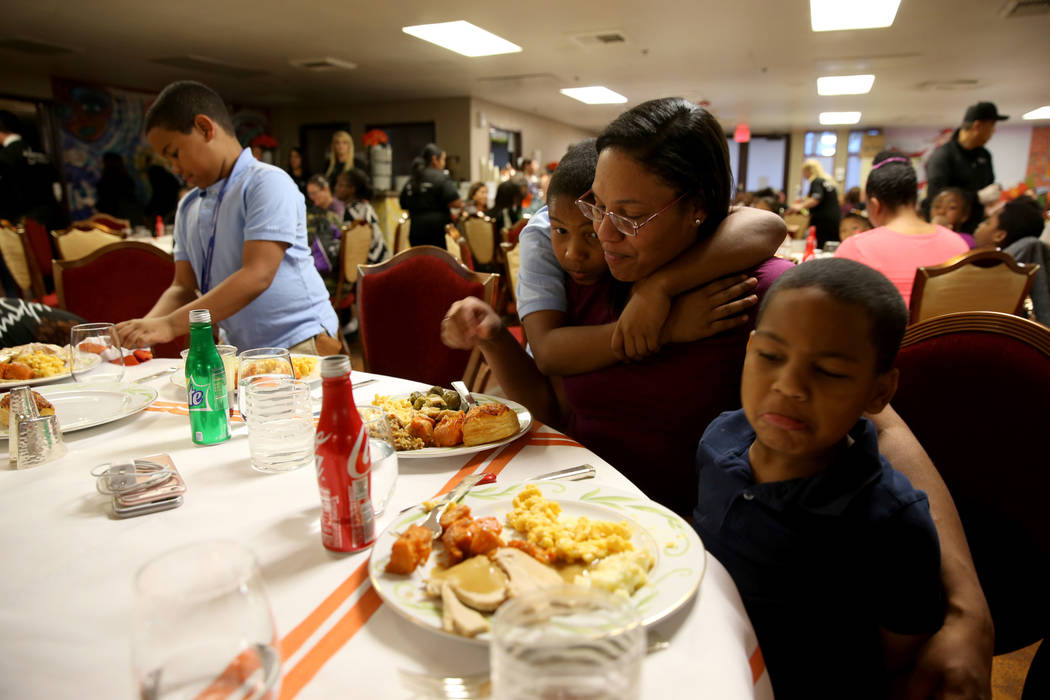 Christine Johnson and her sons Prince, 10, Gregory, 7, and Christion, 5, enjoy Thanksgiving dinner catered by Wynn Las Vegas at the Shade Tree shelter for homeless women and children in Las Vegas ...