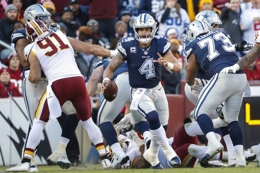 Dallas Cowboys quarterback Dak Prescott (4) scrambles with the ball during the first half of an NFL football game against the Washington Redskins, Sunday, Oct. 21, 2018, in Landover, Md. (AP Photo ...