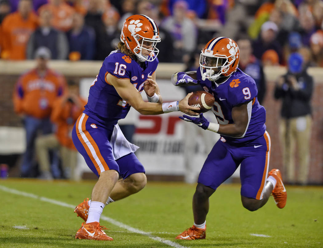 Clemson quarterback Trevor Lawrence hands the ball off to Travis Etienne during the first half of an NCAA college football game against Duke Saturday, Nov. 17, 2018, in Clemson, S.C. Clemson won 3 ...
