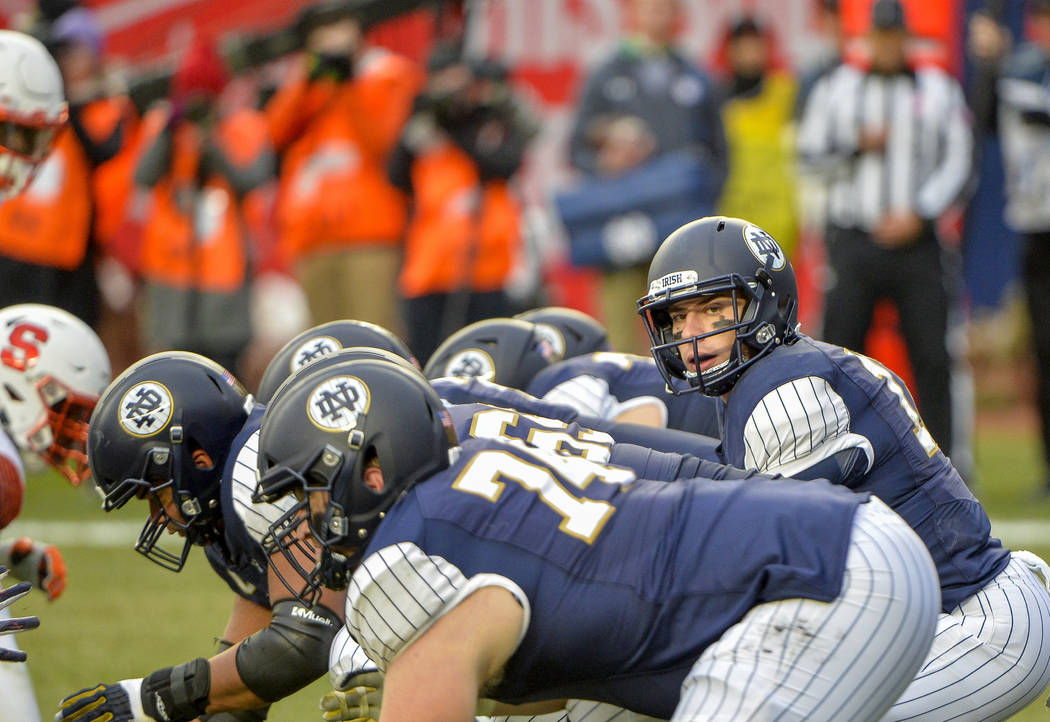 Notre Dame quarterback Ian Book (12) under center in the first quarter of an NCAA college football game against Syracuse, Saturday, Nov. 17, 2018, at Yankee Stadium in New York. (AP Photo/Howard S ...