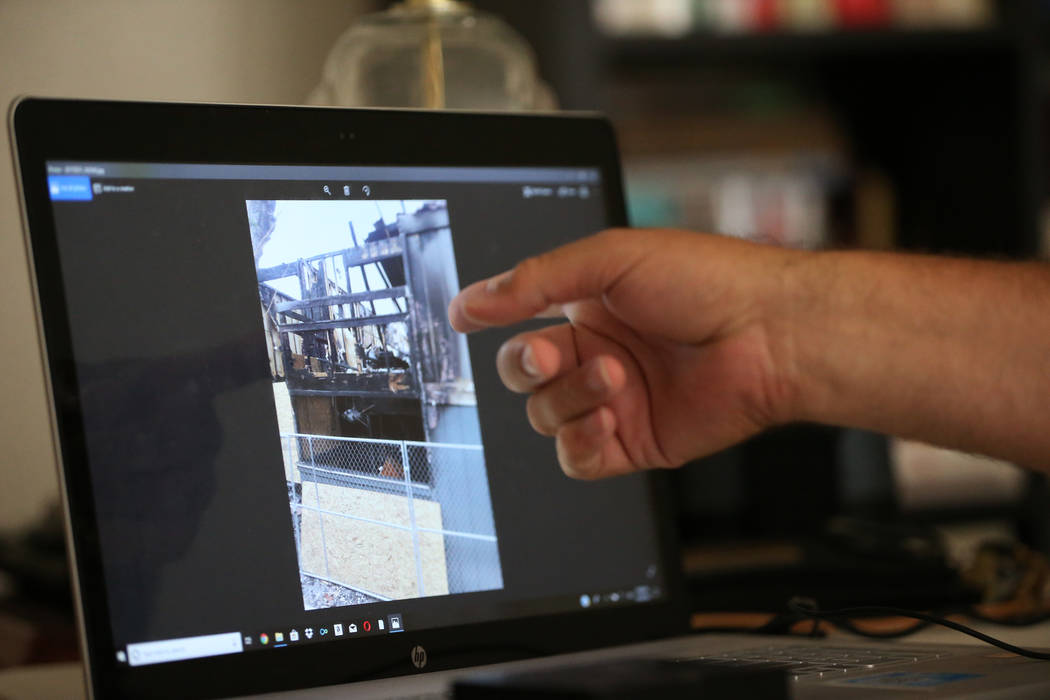 Heath Burkhalter shows a picture of the aftermath of a fire that destroyed his apartment during an interview at his Las Vegas apartment, Thursday, Aug. 30, 2018. Burkhalter was displaced by one of ...