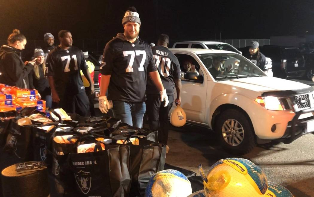 Raiders offensive linemen Kolton Miller (77), Kelechi Osemele (70) and Brandon Parker (75) serve turkey and various Thanksgiving fixings Tuesday night, Nov. 21, 2018, to families at team headquart ...