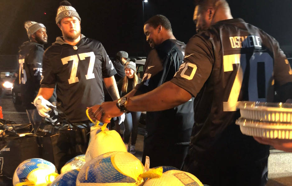 Raiders offensive linemen Kolton Miller (77), Kelechi Osemele (70), Brandon Parker (75) and Justin Murray (71 in background) serve turkey and various Thanksgiving fixings Tuesday night, Nov. 21, 2 ...