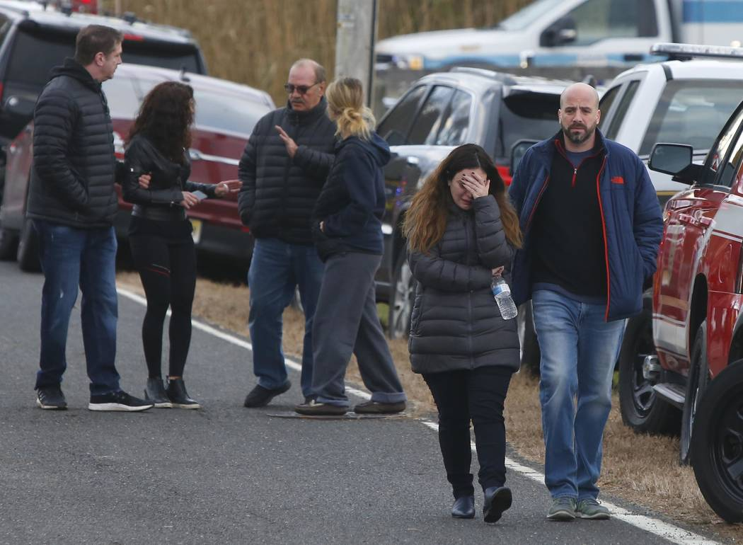 Pedestrians walk away from the scene of a fatal at 15 Willow Brook Rd. Tuesday, Nov. 20, 2018, in Colts Neck,N.J. Authorities say two adults and two children were found dead at the scene of a burn ...
