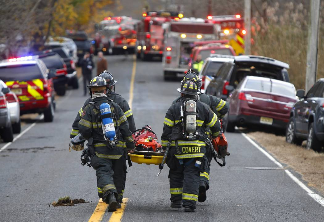 Firefighters carry a stretcher to the scene of a fatal fire at 15 Willow Brook Rd. Tuesday, Nov. 20, 2018, in Colts Neck,N.J. Authorities say two adults and two children were found dead at the sce ...