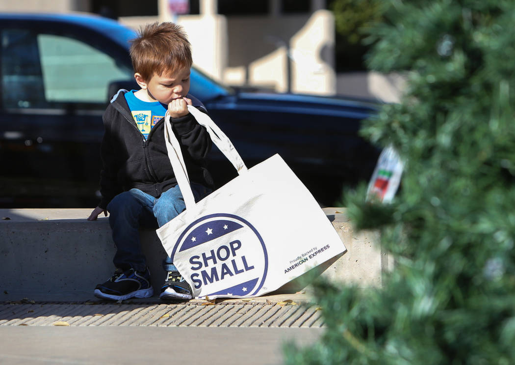 Las Vegas resident Gabriel McGinnis, 3, looks down at a shop small tote bag being given out to attendees during Shop Small Henderson in Henderson, Saturday, Nov. 24, 2018. Caroline Brehman/Las Veg ...