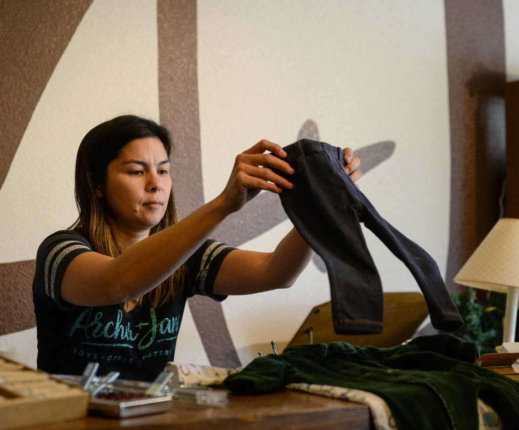Archer + Jane owner Crystal Moses folds up baby clothing for a customer during Shop Small Henderson in Henderson, Saturday, Nov. 24, 2018. Caroline Brehman/Las Vegas Review-Journal