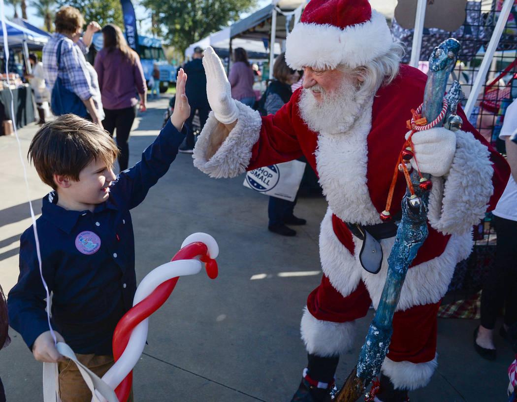 Henderson resident Luke Sisk, 5, goes to high five Bud Slade, dressed up as Santa Claus, during Shop Small Henderson in Henderson, Saturday, Nov. 24, 2018. Caroline Brehman/Las Vegas Review-Journal