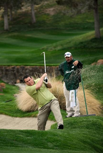 Under the guidance of caddie Chris Pryor, right, Review-Journal sports reporter Todd Dewey takes a shot from the bunker on the first hole at Shadow Creek.