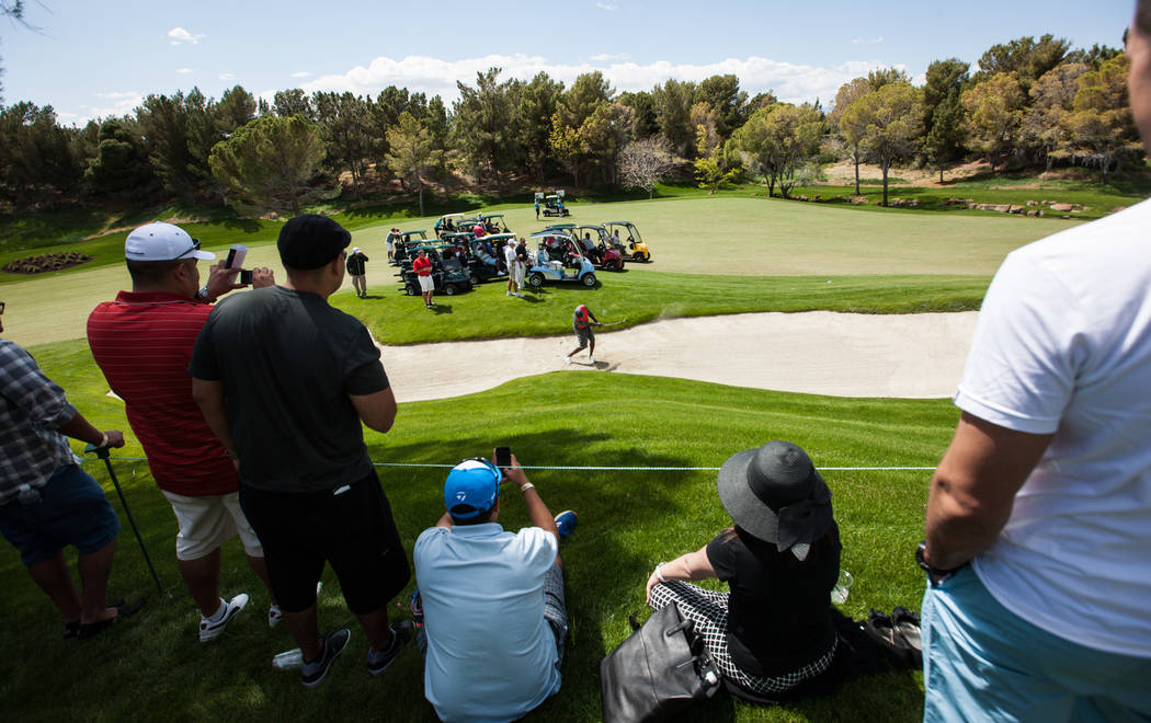 Fans watch as Michael Jordan hits the ball out of a bunker at the 9th hole during the Michael Jordan Celebrity Invitational at Shadow Creek Golf Course in North Las Vegas on Saturday, April 5, 201 ...