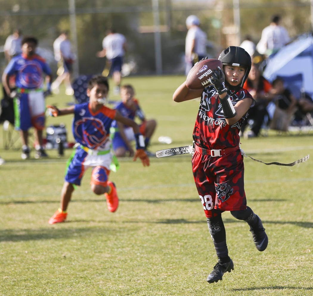 The Apex Predators' Seth Segovia pulls in a reception while playing against the Ballers during a National Youth Sports Nevada flag football game at Aventura Park in Henderson on Saturday, Nov. 17, ...