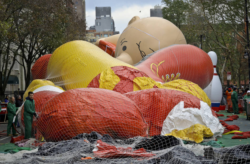 Giant character balloons, including Charlie Brown, are being inflated the night before their appearance in the 92nd Macy's Thanksgiving Day parade, Wednesday Nov. 21, 2018, in New York. (AP Photo/ ...