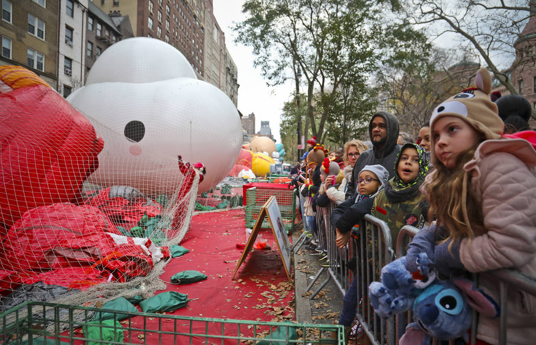 Crowds gather to see giant character balloons being inflated the night before their appearance in the 92nd Macy's Thanksgiving Day parade, Wednesday Nov. 21, 2018, in New York. (AP Photo/Bebeto Ma ...