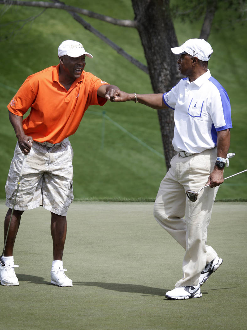 Vince Coleman, left, fist-bumps Ozzie Smith after Smith made a favorable putt at the Michael Jordan Celebrity Invitational at Shadow Creek Golf Course in North Las Vegas on Sunday, Apr. 7, 2013. T ...