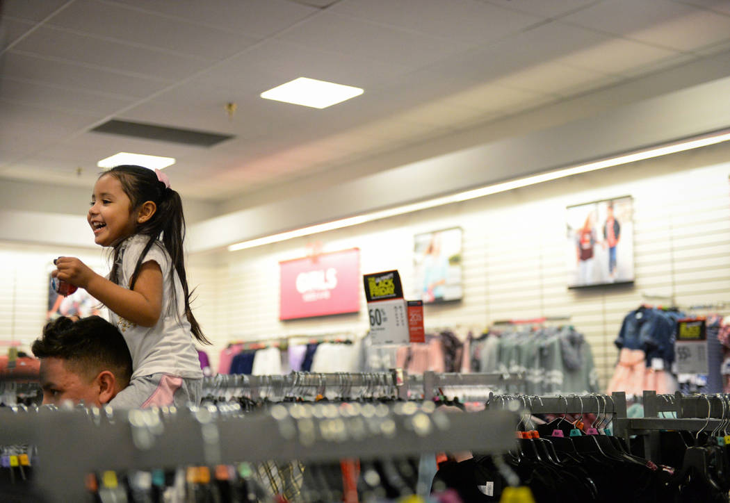 Oswaldo Alvarado carries his daughter, Jarely Chavez, 4, on his shoulders as they walks through the aisles of the J.C. Penney at the Meadows Mall as they hunt for Black Friday deals on Thanksgivin ...