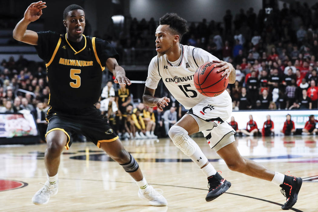 Cincinnati's Cane Broome (15) drives as Milwaukee's Carson Warren-Newsome defends during the second half of an NCAA college basketball game Friday, Nov. 16, 2018, in Cincinnati. (AP Photo/John Min ...