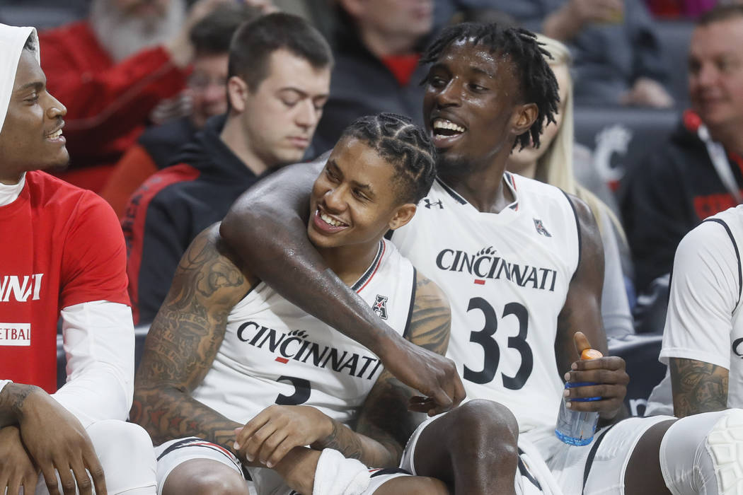 Cincinnati's Justin Jenifer, center left, and Nysier Brooks (33) celebrate on the bench during the second half of an NCAA college basketball game against Western Michigan, Monday, Nov. 19, 2018, i ...