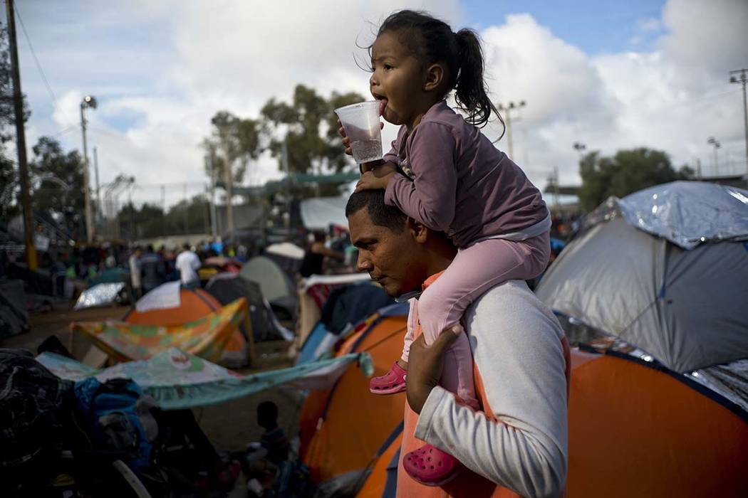 A man carries a girl on his shoulders at a migrant shelter in Tijuana, Mexico, Thursday, Nov. 22, 2018. Several thousand Central American migrants arrived in Tijuana last week more than a month af ...