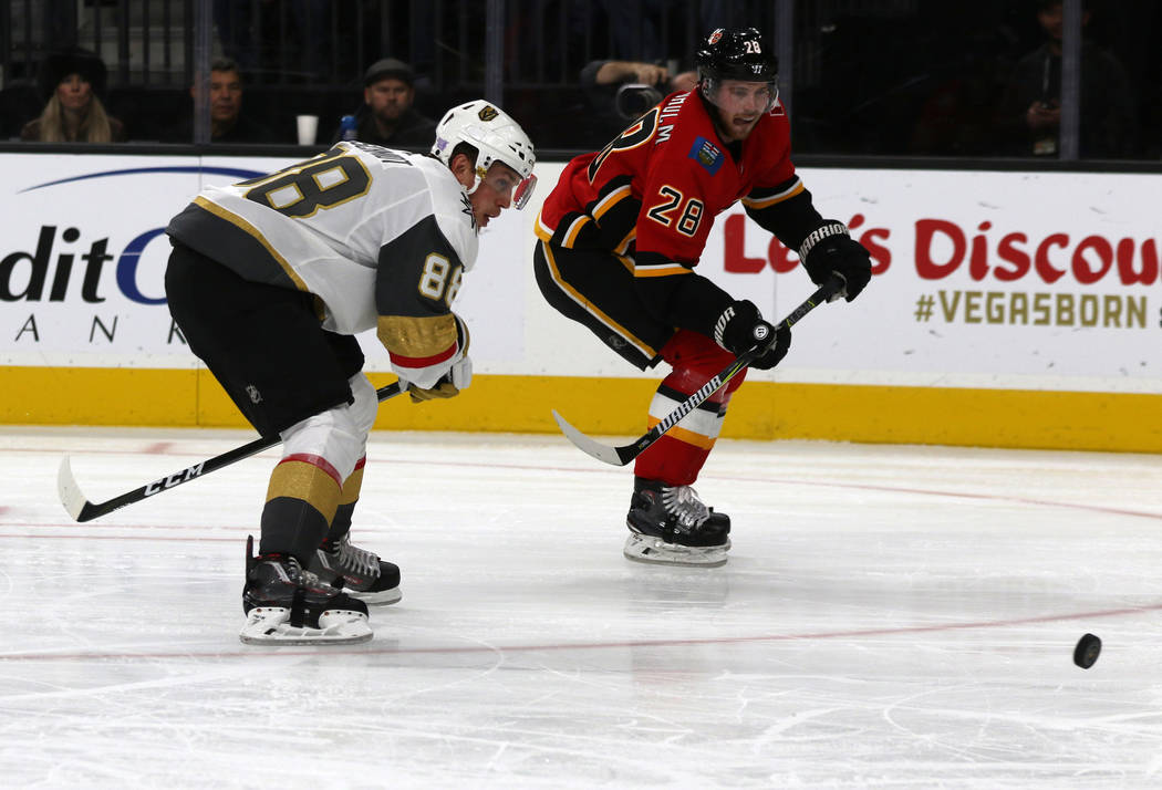 Vegas Golden Knights defenseman Nate Schmidt (88) and Calgary Flames center Elias Lindholm (28) go after the puck during the second period of an NHL game in Las Vegas, Friday, Nov. 23, 2018. Heidi ...