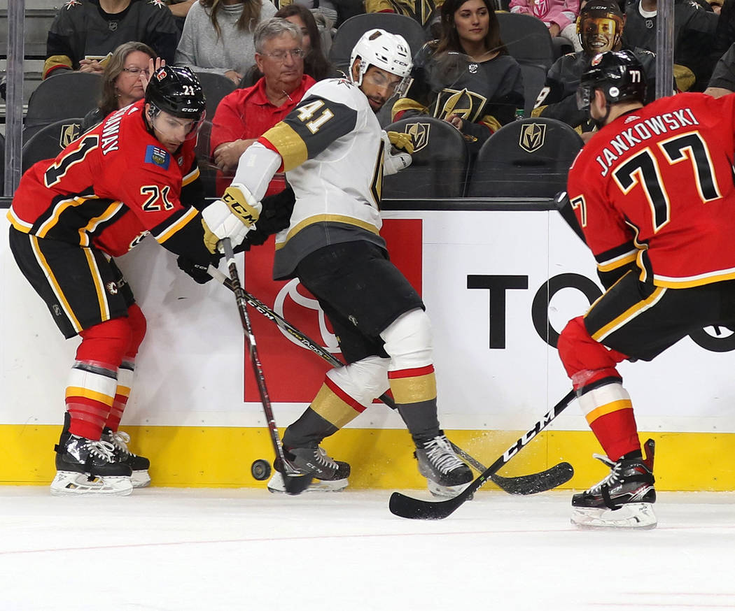 Vegas Golden Knights center Pierre-Edouard Bellemare (41) tries to recover the puck as Calgary Flames right wing Garnet Hathaway (21) fights for it during the first period of an NHL game in Las Ve ...