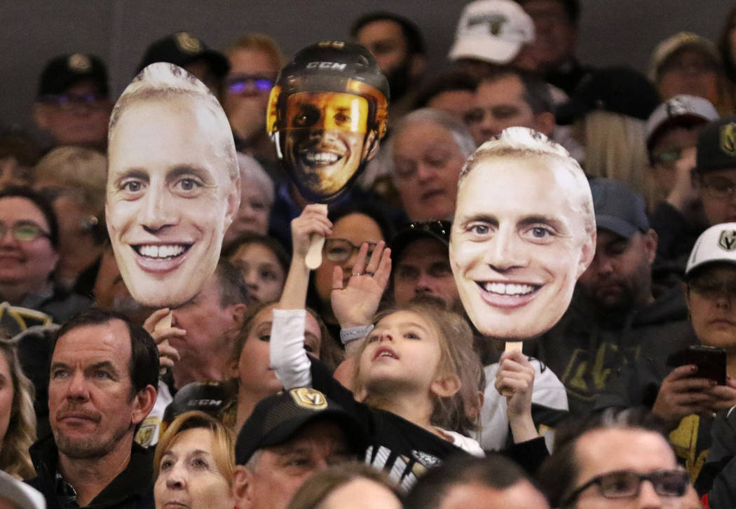 Vegas Golden Knights fans hold up faces of defenseman Nate Schmidt (88) to welcome him back in his first game back at the T-Mobile Arena during the first period of an NHL game against the Calgary ...