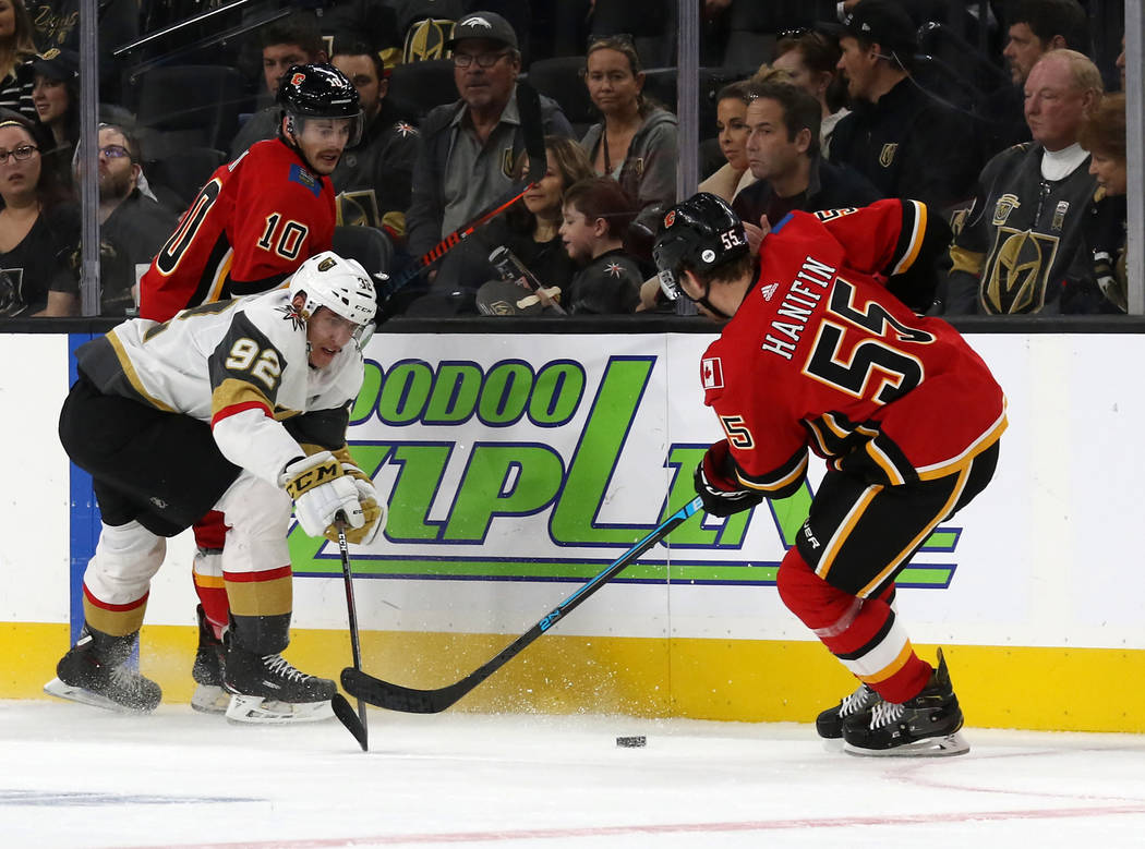 Vegas Golden Knights left wing Tomas Nosek (92) shoots the puck past Calgary Flames defenseman Noah Hanifin (55) as center Derek Ryan (10) defends during the first period of an NHL game in Las Veg ...