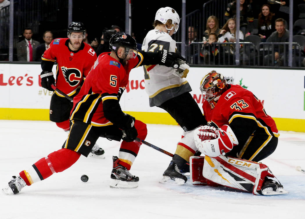 Calgary Flames defenseman Mark Giordano (5) holds Vegas Golden Knights center William Karlsson (71) back from running into goaltender David Rittich (33) during the third period of an NHL game in L ...