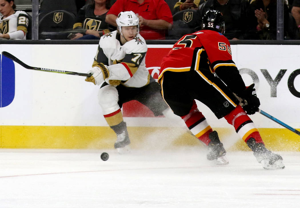 Vegas Golden Knights center William Karlsson (71) shoots the puck past Calgary Flames defenseman Noah Hanifin (55) during the third period of an NHL game in Las Vegas, Friday, Nov. 23, 2018. Heidi ...