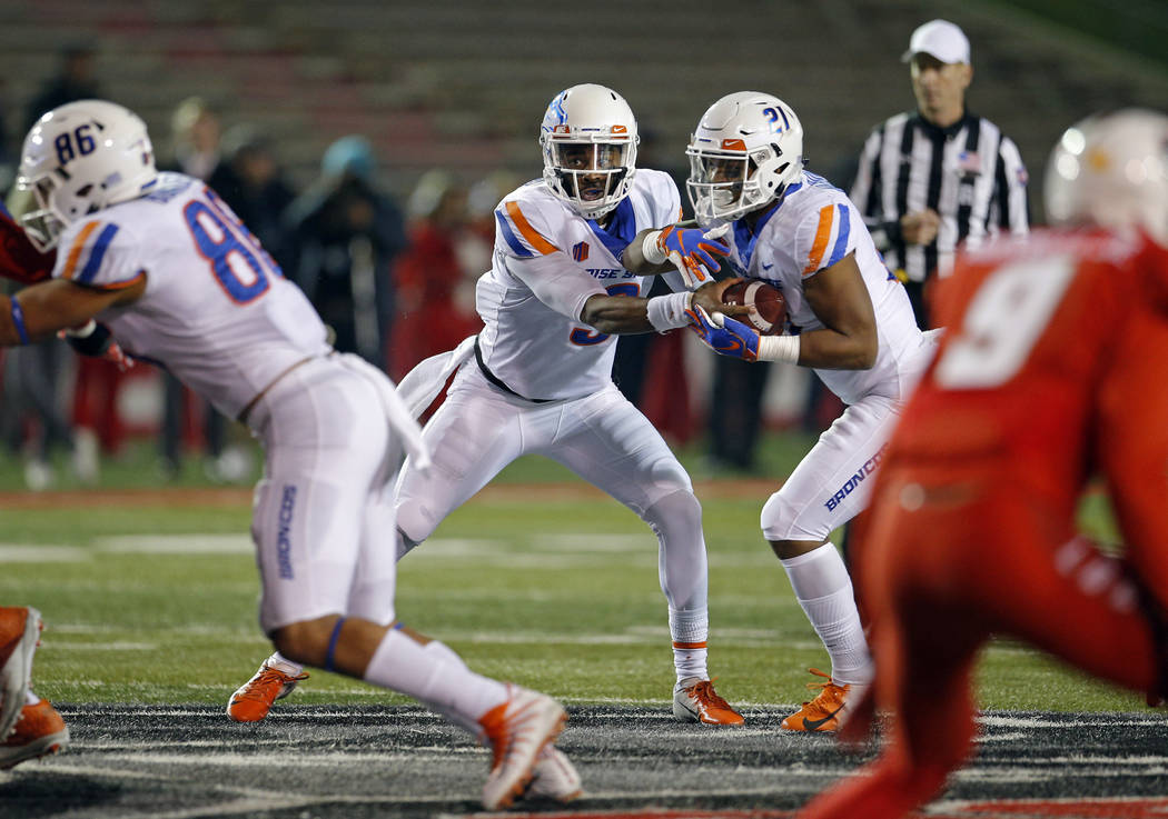 Boise State quarterback Jaylon Henderson (9) feints handing the ball to running back Andrew Van Buren (21) during the second half of an NCAA college football game against New Mexico in Albuquerque ...