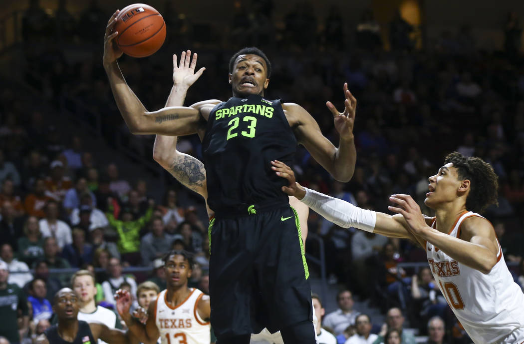 Michigan State's Xavier Tillman (23) gets a rebound next to Texas' Jaxson Hayes, right, during the second half of an NCAA college basketball game Friday, Nov. 23, 2018, in Las Vegas. (AP Photo/Cha ...