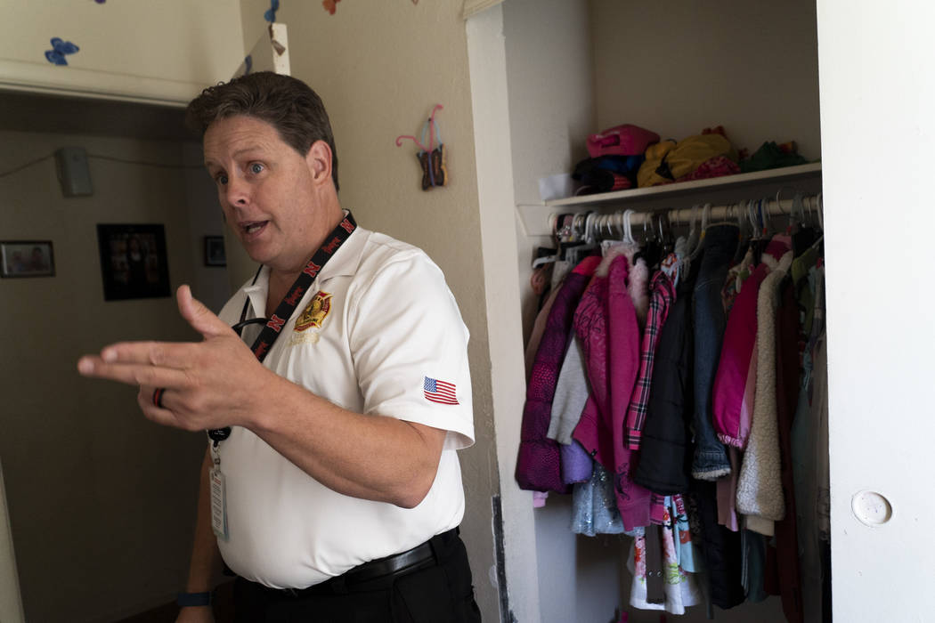 Scott Thompson, fire inspector for Las Vegas Fire and Rescue, talks about fire safety with a family at an apartment complex in the Central Valley off Jones Boulevard in Las Vegas, Thursday, Sept. ...