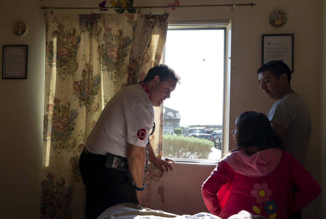 Scott Thompson, fire inspector for Las Vegas Fire and Rescue, instructs a girl and her father on steps to take in the event of a fire at an apartment complex in the Central Valley off Jones Boulev ...