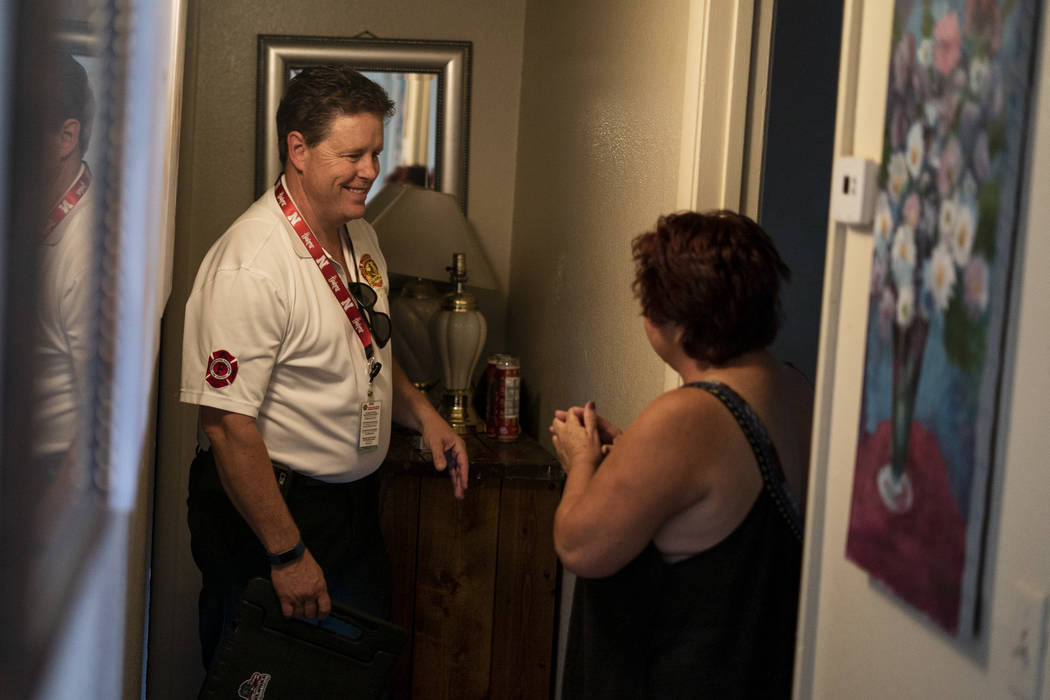 Scott Thompson, fire inspector for Las Vegas Fire and Rescue, speaks with a resident about candlelight safety at an apartment complex in the Central Valley off Jones Boulevard in Las Vegas, Thursd ...