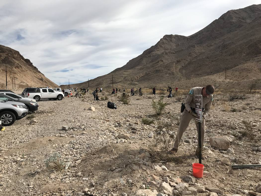 A Bureau of Land Management ranger puts up a new sign along Lake Mead Boulevard near Frenchman Mountain during a volunteer clean-up event Friday. Henry Brean Las Vegas Review-Journal