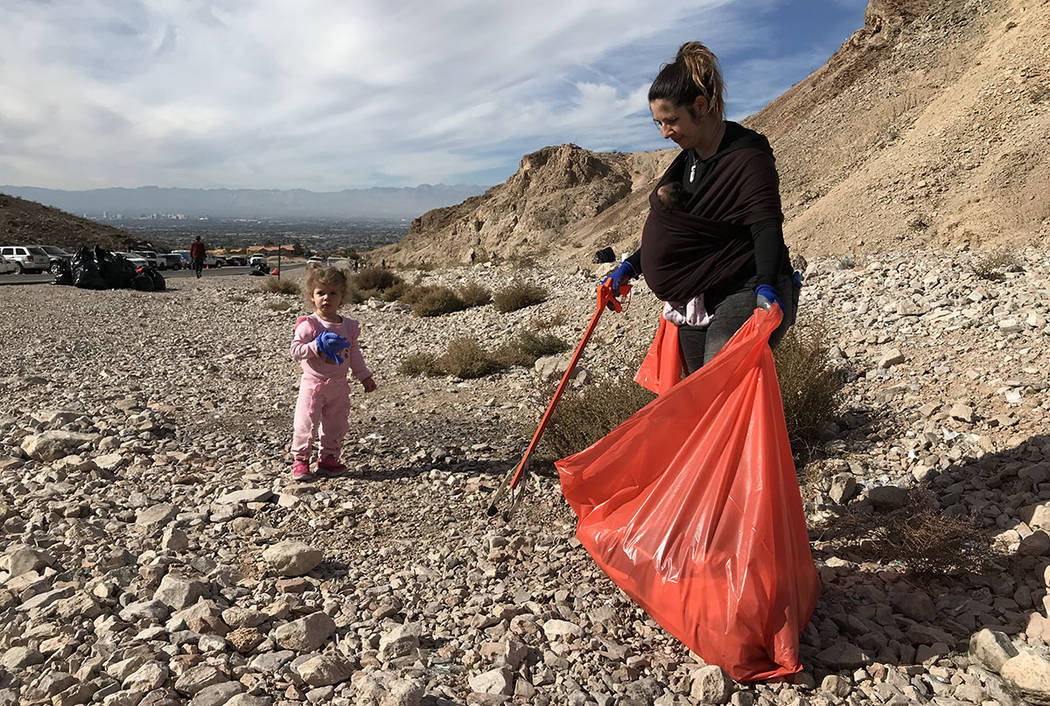 Xandra Magas picks up litter along Lake Mead Boulevard while her daughter, Dalyla, 2, follows her during a volunteer clean-up event Friday. Magas is carrying her 7-week-old daughter, Lilly, strapp ...
