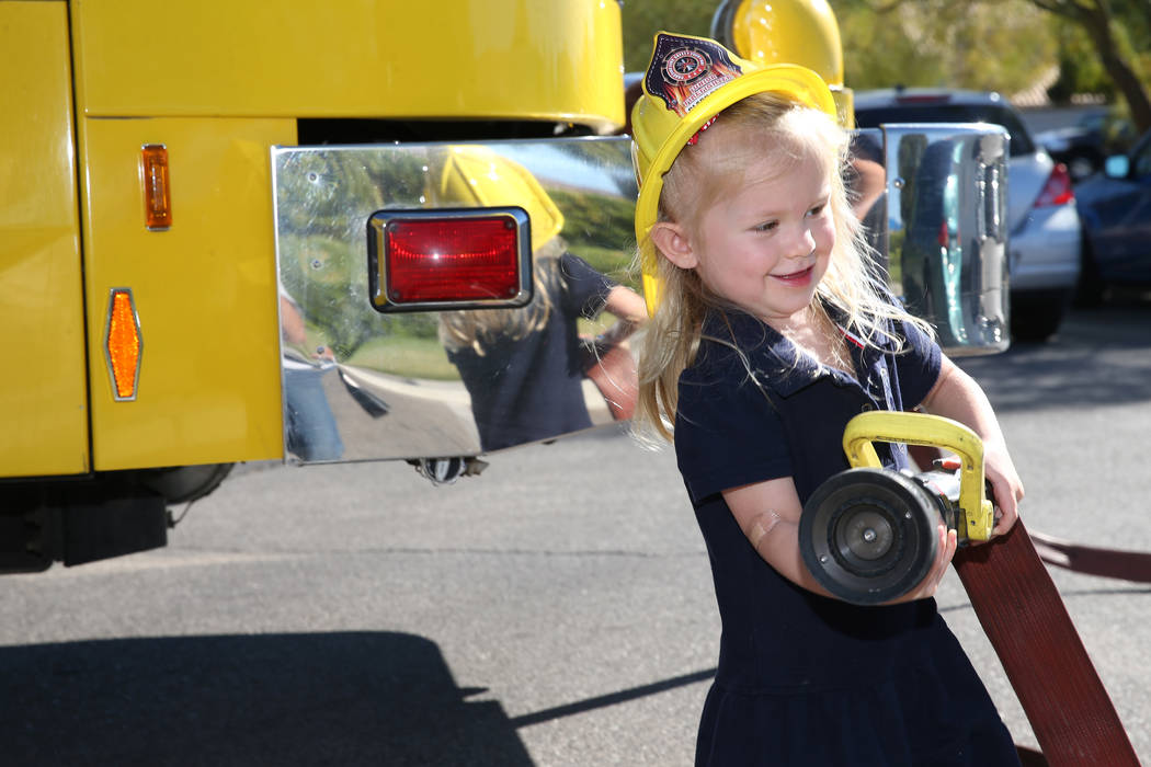 Stella Peck, 4, holds a fire engine water hose during a fire awareness visit by Clark County Fire Department to Merryhill Preschool, 5055 S. Durango Dr., in Las Vegas, Wednesday, Oct. 24, 2018. Er ...
