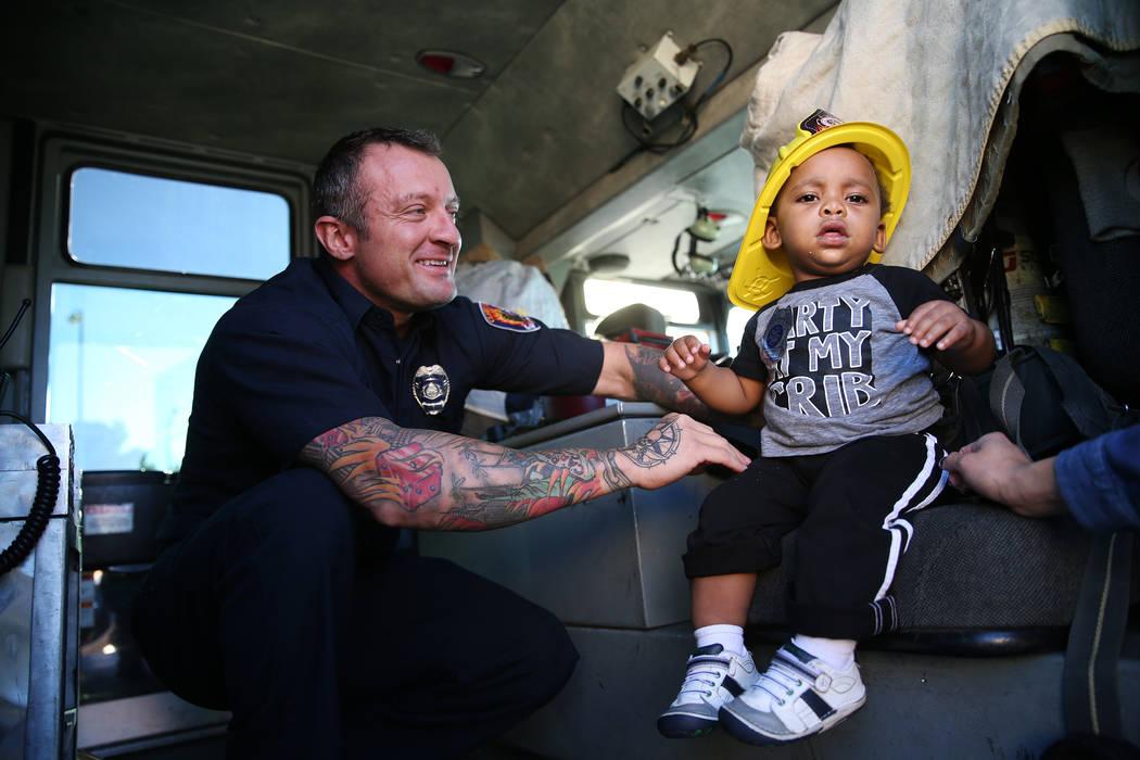 Clark County Fire Department firefighter Jonathan McBreen, left, shows Avery Duncan, 1, inside a fire engine during a fire awareness visit to Merryhill Preschool, 5055 S. Durango Dr., in Las Vegas ...