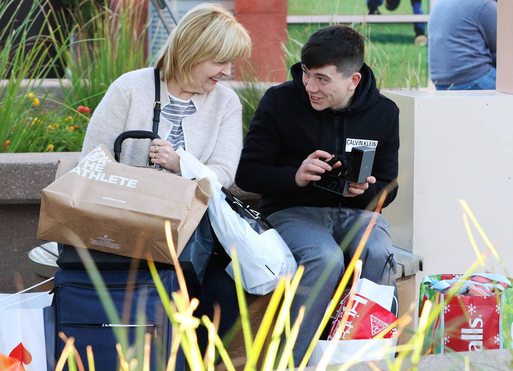 Ronan Crossan shows his new watch to his mother Paulina, both of Ireland, after shopping during Black Friday at the North Premium Outlet Mall on Friday, Nov. 23, 2018. Bizuayehu Tesfaye Las Vegas ...