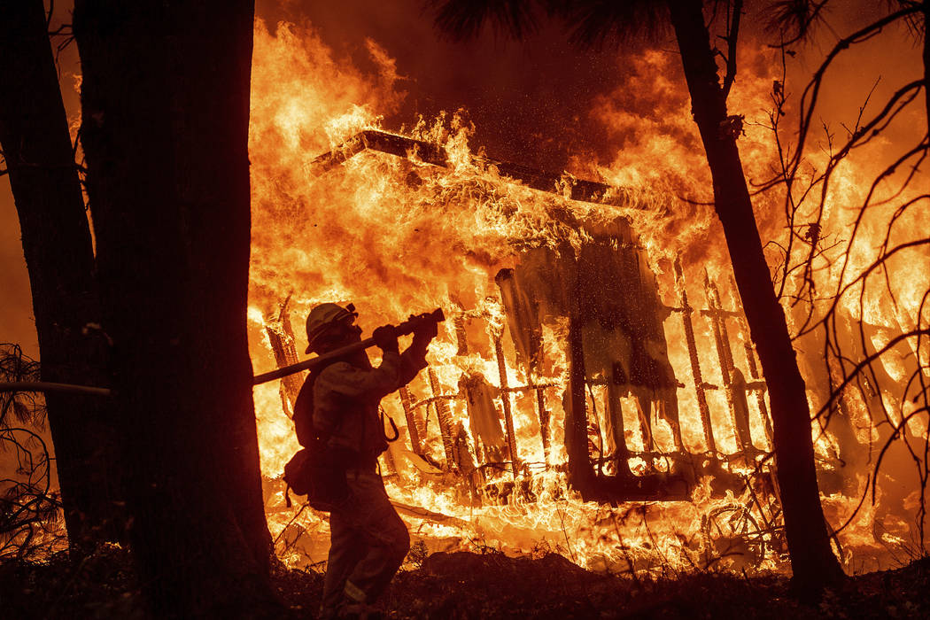 In this Nov. 9, 2018 file photo, firefighter Jose Corona sprays water as flames from the Camp Fire consume a home in Magalia, Calif. A massive new federal report warns that extreme weather disaste ...