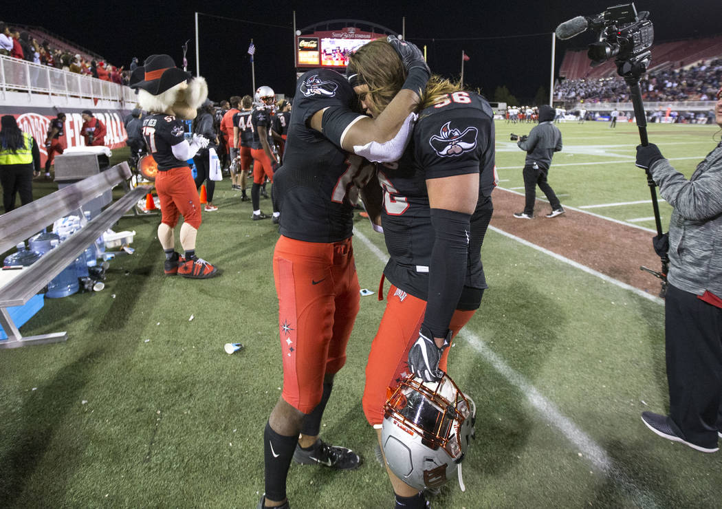 UNLV Rebels linebacker Javin White (16) and defensive lineman Roger Mann (56) share a hug after defeating the Nevada Wolf Pack 34-29 following an NCAA football game at Sam Boyd Stadium in Las Vega ...